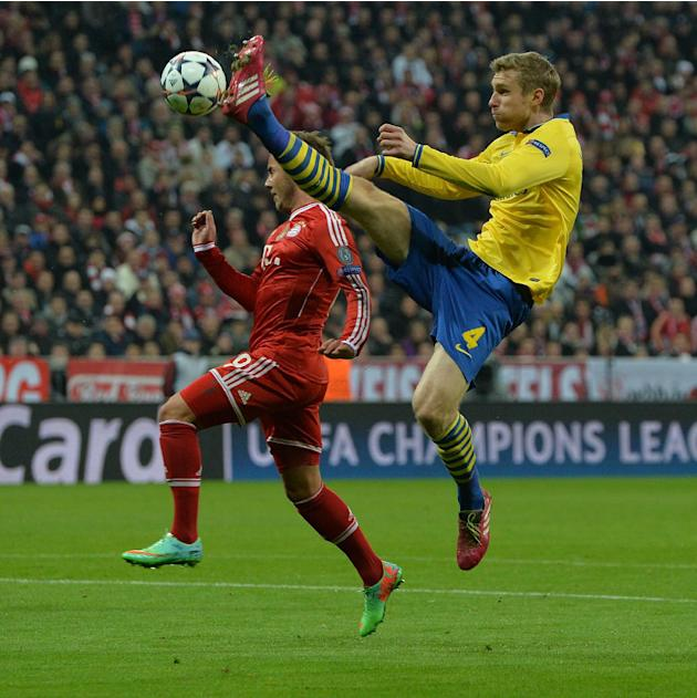 Bayern's Mario Goetze, left, and Arsenal's Per Mertesacker challenge for the ball during the Champions League round of the last 16 second leg soccer match between FC Bayern Munich and Arsenal