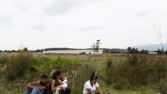 A group of Central American immigrants sit between vegetation for fear of organized crime bands in Huehuetoca, near Mexico City