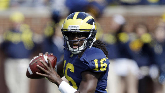 FILE - In this Oct. 1, 2011, file photo, Michigan quarterback Denard Robinson (16) looks to pass during the second quarter of an NCAA college football game against Minnesota in Ann Arbor, Mich. The center of the college football world will be Arlington, Texas on Saturday, when No. 8 Michigan plays No. 2 and defending national champion Alabama at Dallas Cowboys Stadium.(AP Photo/Carlos Osorio, File)