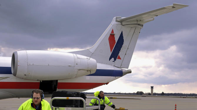In this March 12, 2013 photo, baggage handlers unload an American Eagle jet after it landed at the Abraham Lincoln Capital Airport in Springfield, Ill. The airport is one of nearly 240 small airports around the country that will likely shut down their air traffic control towers under federal budget cuts, stripping away a layer of safety during takeoffs and landings and leaving many pilots to manage the most critical stages of flight on their own. (AP Photo/Seth Perlman)