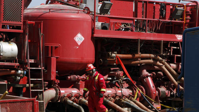 FILE- In this photograph taken April 15, 2009, an unidentified worker steps through the maze of hoses being used at a remote fracking site being run by Halliburton for natural-gas producer Williams in Rulison, Colo. The U.S. Environmental Protection Agency announced Thursday Dec. 8, 2011 in Wyoming, for the first time that fracking - a controversial method of improving the productivity of oil and gas wells - may be to blame for causing groundwater pollution. (AP Photo/David Zalubowski, File)