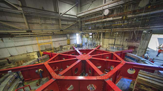 A June 4, 2013, photo provided by Brookhaven National Laboratory shows a red stabilizing apparatus that will be used to transport a 50-foot-wide electromagnet storage ring, at Brookhaven National Laboratory in Upton, N.Y., on eastern Long Island. The ring, which will capture subatomic particles that live only 2.2 millionths of a second, will be transported in one piece, and moved flat, to its new home at the U.S. Department of Energy's Fermi National Accelerator Laboratory in Batavia, Ill.   (AP Photo/Brookhaven National Laboratory)