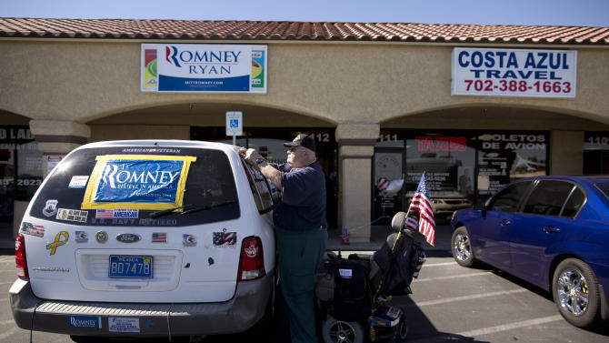 Skip Royeton tapes a new Mitt Romney poster to the window of his car outside a Romney campaign office, Saturday, Oct. 20, 2012, in Las Vegas. Romney officials argue that Hispanics, who suffer from a 9.9 percent unemployment rate, more than 2 points higher than the national rate, are naturally drawn to the GOP ticket. But some Romney supporters are pessimistic that Republicans can make inroads with a population that, many polls show, favors Obama by a 2-1 margin.  (AP Photo/Julie Jacobson)