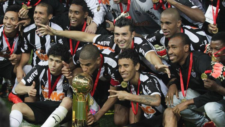 Silva of Atletico Mineiro kisses the trophy as he celebrates with team mates after defeating Lanus in their Recopa Sudamericana final soccer match in Belo Horizonte