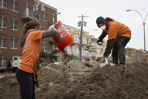 Volunteers work to remove sand from streets in the Rockaways, Saturday, Nov. 10, 2012, in the Queens borough of New York. Despite power returning to many neighborhoods in the metropolitan area after S
