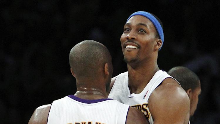 Los Angeles Lakers guard Kobe Bryant (24) and center Dwight Howard (12) celebrate their 105-96 win over the Oklahoma City Thunder in an NBA basketball game in Los Angeles, Sunday, Jan. 27, 2013. (AP Photo/Reed Saxon)