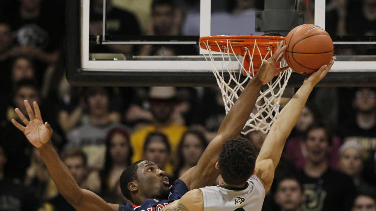 Arizona forward Solomon Hill, left, reaches up to block a shot by Colorado guard Askia Booker in the first half of an NCAA college basketball game in Boulder, Colo., Thursday, Feb. 14, 2013. (AP Photo/David Zalubowski)