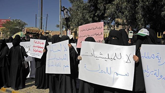 ARH-10. Sana'a (Yemen), 27/12/2014.- Yemeni female protesters hold anti-Shiite militia placards reading 'No to the rule of militias Yes to civil state' (L) and 'No to militias Yes to State' (R) during a rally against the Shiite Houthi insurgency, in Sana'a, Yemen, 27 December 2014. The Iran-backed Shiite Houthi movement has spread throughout Yemen since its armed militias took over large parts of the country and its military power centers in September (Protestas) EFE/EPA/YAHYA ARHAB