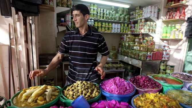 A Palestinian vendors displays food, including pickled vegetables and olives, in preparation for Ramadan at a market in the West Bank city of Hebron, Saturday, June 28, 2014. Muslims throughout the world are preparing themselves for the holy month of Ramadan, when the observant fast from dawn till dusk. (AP Photo/Majdi Mohammed)
