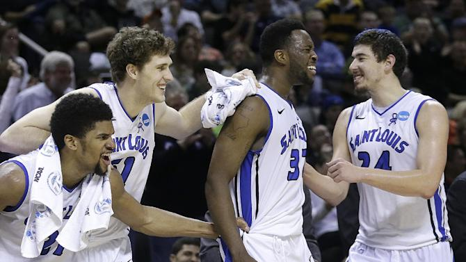 Saint Louis forwards Dwayne Evans, from left, Rob Loe, Cory Remekun, and Cody Ellis celebrate on the bench during the second half of a second-round game in the NCAA college basketball tournament against New Mexico State in San Jose, Calif., Thursday, March 21, 2013. Saint Louis won 64-44. (AP Photo/Jeff Chiu)
