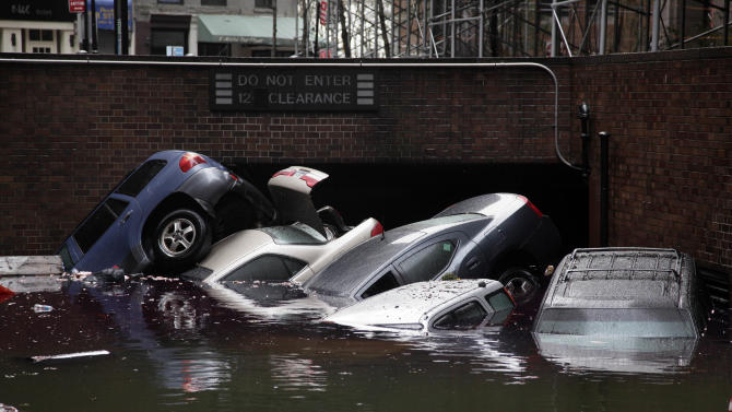 FILE -In this Tuesday, Oct. 30, 2012, file photo, cars are submerged at the entrance to a parking garage in New York's Financial District in the aftermath of superstorm Sandy. Alarming claims that hundreds of thousands of flood-damaged cars from Superstorm Sandy will inundate the used car market aren't backed up by insurance company claim data, The Associated Press has found. The dire predictions come mostly from companies that track vehicle title and repair histories and sell those reports.(AP Photo/Richard Drew)