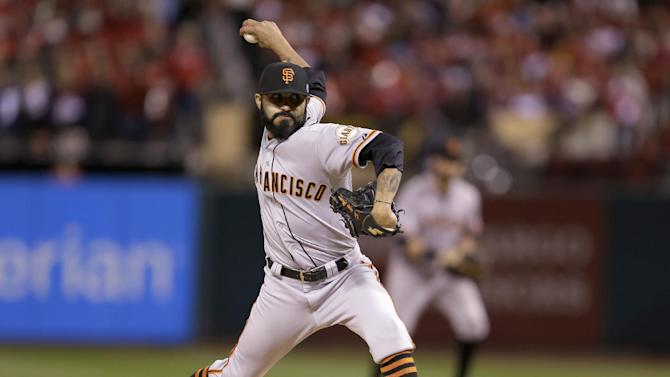 FILE - In an Oct. 11, 2014, file photo San Francisco Giants' Sergio Romo throws during the eighth inning in Game 1 of the National League baseball championship series against the St. Louis Cardinals in St. Louis.  A person with knowledge of the negotiations says Wedensday Dec. 17, 2014, free agent reliever  Romo is closing in on a new contract with the San Francisco Giants.  (AP Photo/Jeff Roberson, file)