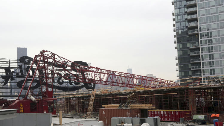 "A mangled crane lies at the construction site in the Queens borough of New York where it collapsed, Wednesday, Jan. 9, 2013, behind a big neon ""Pepsi Cola"" sign, a local landmark. The Fire Department of New York says the 200-foot crane collapsed onto a building under construction, injuring seven people, three of them seriously. (AP Photo/Mary Altaffer)"