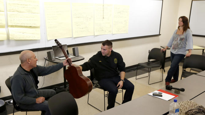 In this Oct. 10, 2012, photo, musician Julio Fernandez, left, hands a guitar to U.S. Navy Petty Officer Mike Cordes during a class session at Montclair State University in Montclair, N.J. Students are participating in a music class for servicemen and women that helps them cope with their life after the military through a program called Voices of Valor. (AP Photo/Julio Cortez)