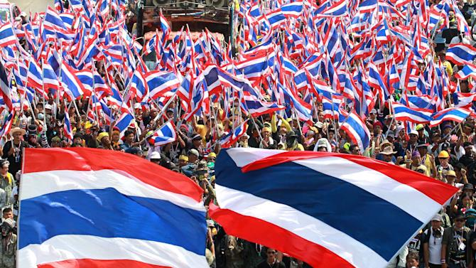 Anti-government protesters wave Thai national flags during a rally at the Department of Special Investigation (DSI) on the outskirts of Bangkok, Thailand, Monday, Dec. 23, 2013. About 5,000 protesters took part in the rally and later stormed in to the DSI office building when the DSI has charged the protest leaders on illegal demonstrations and frozen their bank accounts last week. (AP Photo/Wason Wanichakorn)