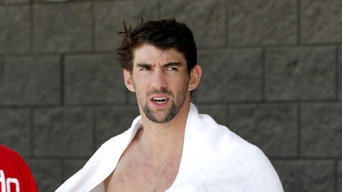 Michael Phelps dries off after warm ups prior to competing in the 100-meter butterfly during the Arena Grand Prix, Thursday, April 24, 2014, in Mesa, Ariz. It is Phelps' first competitive event after a nearly two-year retirement. (AP Photo/Matt York)