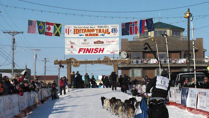 In this photo taken Wednesday March 13, 2013, in Nome, Alaska, residents greet Kotzebue musher John Baker as he nears the finish line. Long after the winner has been crowned, Nome residents honor each musher who finishes the race, day or night. (AP Photo/Mark Thiessen)