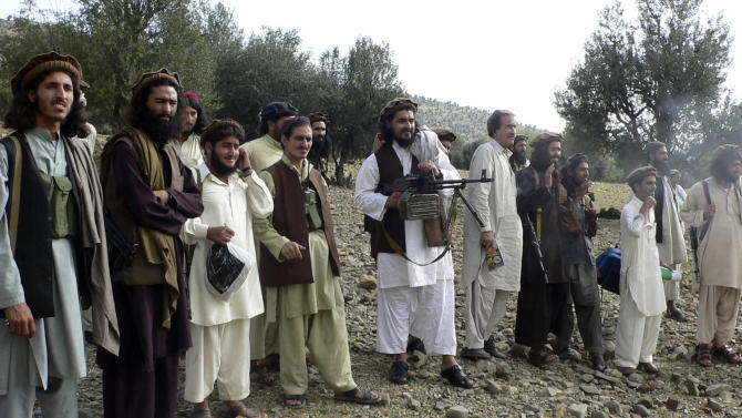 FILE - In this file image taken on Oct. 4, 2009, Pakistan's new Taliban leader Hakimullah Mehsud, center, operates light machine gun with his comrades in Sararogha in Pakistani tribal area of South Waziristan along Afghanistan border. Intelligence officials said Friday, Nov. 1, 2013 that the leader of the Pakistani Taliban Hakimullah Mehsud was one of three people killed in a U.S. drone strike. (AP Photo/Ishtiaq Mahsud, File)