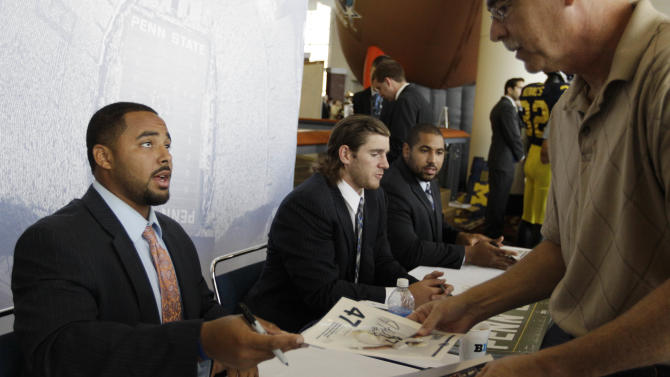 Penn State football players Jordan Hill, left, Michael Mauti and John Urschel, right, sign autographs for fans as part of Big Ten Media Days and Kickoff Luncheon, Friday, July 27, 2012, in Chicago. (AP Photo/M. Spencer Green)