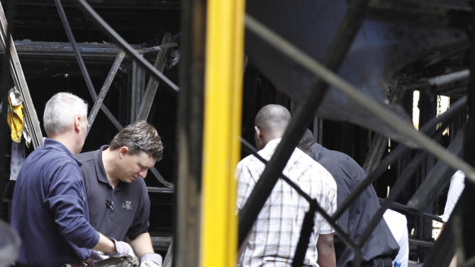 "American investigators, left, assists Kenyan officials, right, in Nairobi, Kenya, Monday, May 29, 2012, in their investigation into a large explosion in Nairobi, Monday. An explosion ripped through a building full of small shops in downtown Nairobi, injuring at least 33 people, including a woman who blamed the blast on a ""bearded man"" who left behind a bag shortly before the detonation. (AP Photo/Khalil Senosi)"