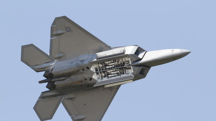 FILE - In this April 30, 2012, file photo, an Air Force F-22 Raptor displays it's weapons bays as it goes through maneuvers during a demonstration at Langley Air Force Base in Hampton, Va., Monday, April 30, 2012. Two members of Congress said Thursday, June 14, 2012, that new information provided by the Air Force shows an oxygen-deficit problem on F-22 fighter jets is worse than previously disclosed. (AP Photo/Steve Helber, File)