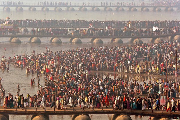 Hindu devotees walk across pontoon bridges to take a holy dip at Sangam, the confluence of the Ganges, Yamuna and mythical Saraswati River, during the Maha Kumbh festival, in Allahabad, India , Sunday