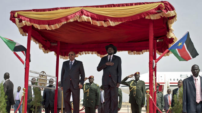 Sudan's President Omar al-Bashir, center-left, and South Sudan's President, Salva Kiir, center, listen to South Sudan's national anthem after al-Bashir arrived in Juba, South Sudan, on Friday, April 12, 2013.  Sudanese President Omar al-Bashir traveled to South Sudan on Friday for the first time since the south peacefully broke away from Sudan in 2011, and South Sudan's president says he and al-Bashir have agreed to a resumption of oil exports and border trade. (AP Photo/Mackenzie Knowles-Coursin)