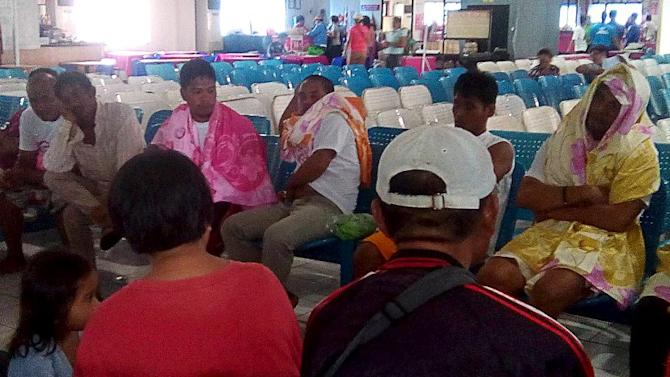 Survivors of the capsized MBCA Kim-Nirvana ferry wait at a ferry passenger area after they were rescued by members of the Philippine Coast Guard in Ormoc city