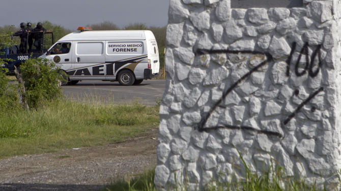 Federal police on a vehicle guard one of the three forensic trucks where several bodies were placed after dozens of bodies, some of them mutilated, were found on a highway connecting the northern Mexican metropolis of Monterrey to the U.S. border found in the town of San Juan near the city of Monterrey, Mexico,  Sunday, May 13, 2012. (AP Photo/Christian Palma)