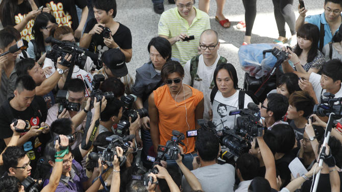 Hong Kong actor Nicholas Tse, center, is surrounded by media after arriving Hong Kong airport from Malaysia Friday, July 8, 2011. Tse was asked about his marital problems with Hong Kong actress Cecilia Cheung, which had been reported in the Chinese media for weeks. (AP Photo/Kin Cheung)