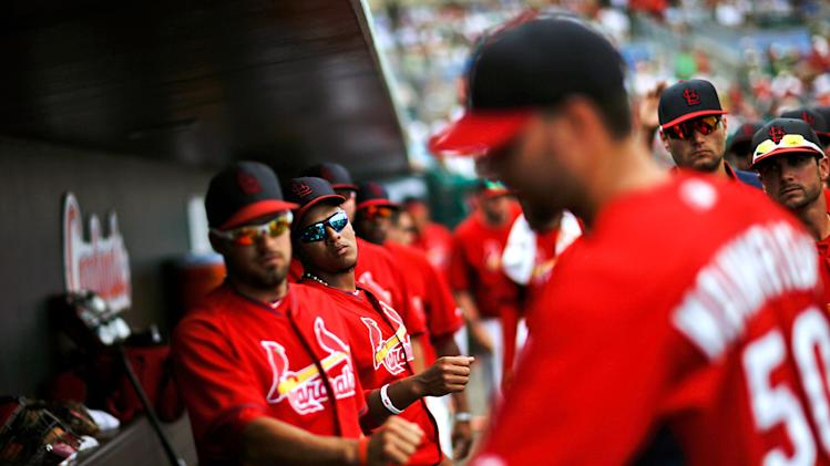 Teammates wait to fist-bump St. Louis Cardinals starting pitcher Adam Wainwright, right, as he walks into the dugout upon being relieved in the fifth inning of an exhibition spring training baseball game against the New York Mets, Sunday, March 16, 2014, in Jupiter, Fla. (AP Photo/David Goldman)