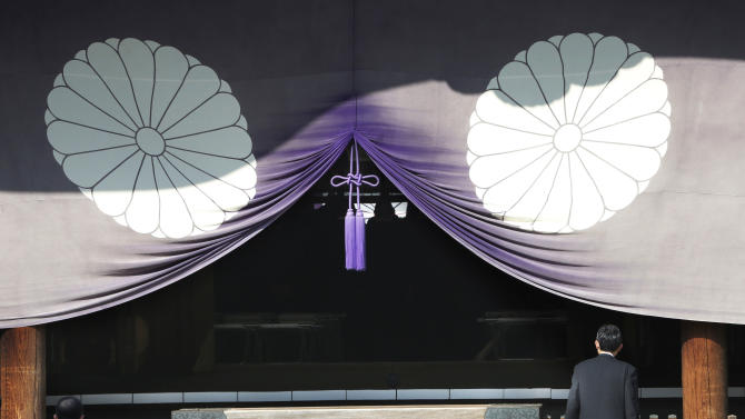 A group of Japanese lawmakers, seen silhouetted in the middle of the photo, offer prayers at the Yasukuni Shrine, which honors Japan's war dead, including World War II leaders convicted of war crimes, in Tokyo during an annual spring festival on Tuesday, April 23, 2013. Dozens of Japanese lawmakers paid homage at the national war shrine Tuesday morning, risking more anger from neighbors South Korea and China over visits they see as failures to acknowledge Japan's militaristic past. (AP Photo/Koji Sasahara)