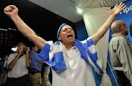 A New Democracy (ND) party supporter celebrates as he watches exit polls at the party&#39;s main election campaign booth in Athens on June 17, 2012. Greece&#39;s two main pro-bailout parties clinched enough votes to form a government in a cliffhanger election on Sunday, easing fears the country will crash out of the euro