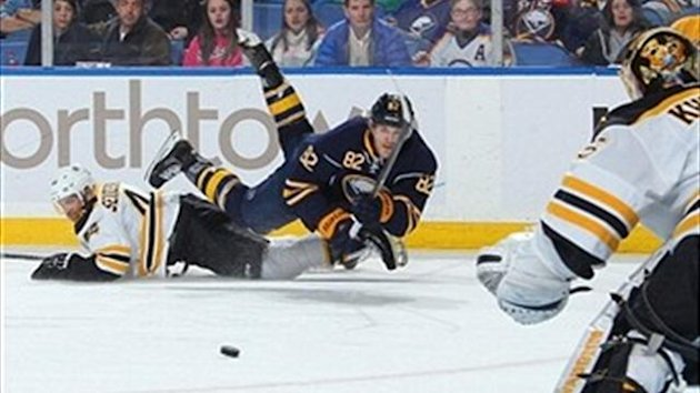 Marcus Foligno (no. 82) of the Buffalo Sabres sends a pass to the front of the net guarded by Anton Khudobin (no. 35) of the Boston Bruins while being upended by Dennis Seidenberg (no. 44).
