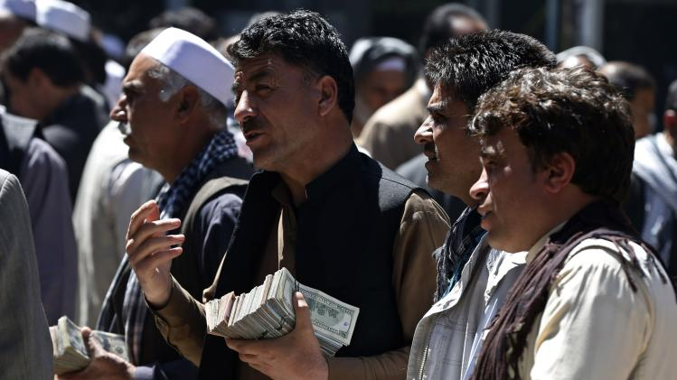 Afghan money changers offer Afghanis for sale at Kabul's largest money market