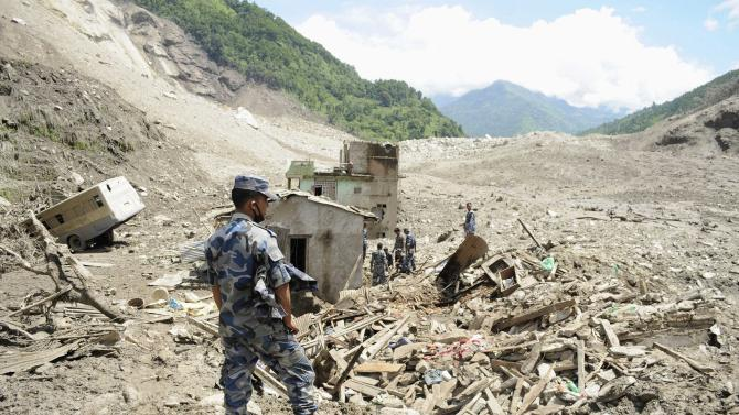 A rescue team from the Armed Police Force stands near damaged houses in the landslide area in Sindhupalchowk district