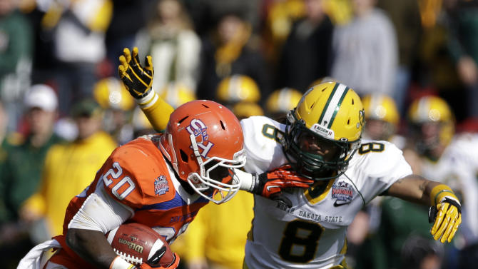 Sam Houston State's Tim Flanders (20) attempts to break a tackle by North Dakota State's Andre' Martin Jr. (8) after gaining yardage following a long reception during the first half of the FCS Championship NCAA college football game, Saturday, Jan. 5, 2013, in Frisco, Texas. (AP Photo/Tony Gutierrez)