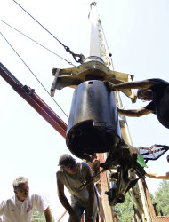 In this Aug. 7, 2012 photo, Randy Grebke of Kohnen Concrete Products, left, helps out with a water well drilling crew on a site which he witched for water in Huey, Ill. Many well drillers still witch or divine for water, Gebke included. Some, like Gebke, use small wires, others have a preference for a particular kind of wood. Many find themselves busier than they have been in years as drought grips much of the country. (AP Photo/Seth Perlman)