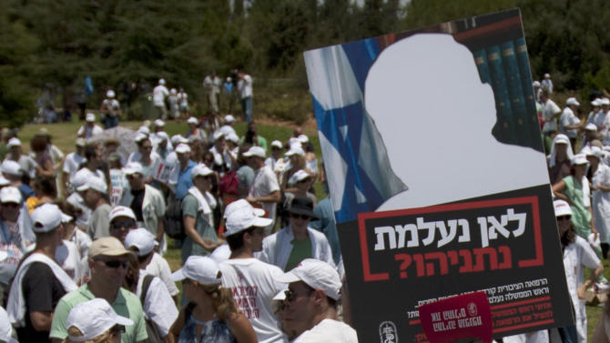 "Israeli medical staff demonstrate in front of the Knesset, Israel's parliament, background in Jerusalem, Sunday, July 31, 2011. Hundreds of Israel's doctors are demonstrating in Jerusalem, stepping up their protest for higher wages and better hospital conditions. The banner in the picture carries a cutout of Israeli Prime Minister Benjamin Netanyahu reads in Hebrew: "" Where did you disappear, Netanyahu ? "" . (AP Photo/Sebastian Scheiner)"