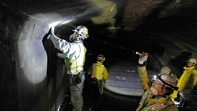 Workers inspect the structure inside the 8.5-kilometer (5.3-mile) Enasan Tunnel on the Chuo Expressway in Achimura, Nagano Prefecture, central Japan, Monday morning, Dec. 3, 2012. Concrete ceiling panels fell onto moving vehicles deep inside another tunnel on the same epressway Sunday, and authorities confirmed nine deaths before suspending rescue work Monday while the roof was being reinforced to prevent more collapses. (AP Photo/Kyodo News) JAPAN OUT, MANDATORY CREDIT, NO LICENSING IN CHINA, FRANCE, HONG KONG, JAPAN AND SOUTH KOREA