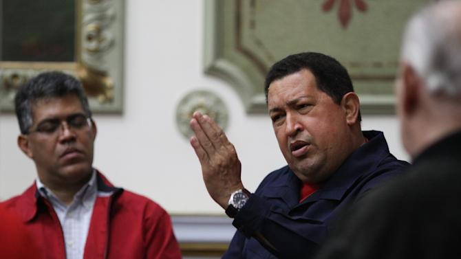 "In this photo released by Miraflores Press Office, Venezuela's President Hugo Chavez speaks during a televised program from the Miraflores presidential palace in Caracas, Venezuela, Wednesday April 11, 2012. Chavez returned to Venezuela Wednesday night and said he's ""doing well"" following cancer treatment in Cuba. Chavez flew to Cuba last week for his third round of radiation therapy. Pictured left is Venezuela's Vice President Elias Jaua. (AP Photo/Miraflores Presidential Office)"