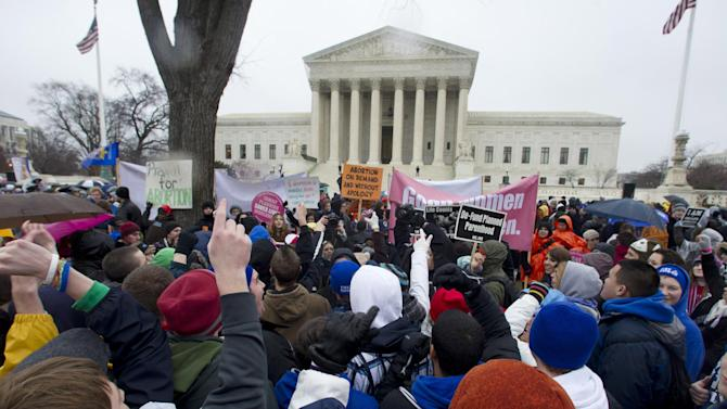 """FILE - In this Jan. 23, 2012, file photo, anti-abortion and abortion rights supporters stand face to face in front of the Supreme Court in Washington, Monday, Jan. 23, 2012, during the annual March For Life rally. There's been a lot of heated talk this year by Democrats contending that Republicans are waging a """"war on women."""" That's hyperbole, retorts the GOP, but there are indeed stark differences between the two parties over these volatile issues. However, the next president _ Obama or Romney _ could have huge influence over the future of abortion policy if vacancies arise on the Supreme Court. For example, if two seats held by liberal justices were vacated and filled by Romney-nominated conservatives, prospects for a reversal of Roe v. Wade would increase. (AP Photo/Manuel Balce Ceneta, File)"""