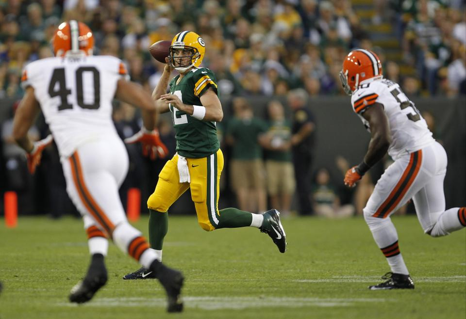Green Bay Packers quarterback Aaron Rodgers scrambles while being rushed by Cleveland Browns' L.J. Fort (40) and  James-Michael Johnson (50) during the first half of a preseason NFL football game Thursday, Aug. 16, 2012, in Green Bay, Wis. (AP Photo/Mike Roemer)