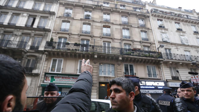 Kurdish activists gather outside a building where three Kurdish women were shot dead, in Paris, Thursday, Jan. 10, 2013. Police say three Kurdish women have been shot dead at a pro-Kurdish centre in Paris in what the French interior minister is calling an execution. (AP Photo/Jacques Brinon)