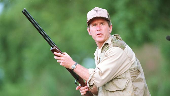 """FILE - In this Sept. 1, 1994 file photo, George W. Bush looks to the sky during a dove hunt  in Hockley, Texas during his first Texas gubernatorial campaign. Anticipating some dove hunting on a 100-plus degree day during Sept. 2000, Bush explained that the birds could be marinated, but """"I'm probably just going to throw them right on the grill."""" (AP Photo/File, David J. Phillip, file)"""