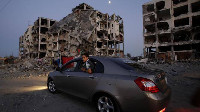 A Palestinian boy surveys the destruction of buildings at a residential neighborhood, in Beit Lahiya, northern Gaza Strip, Thursday, Aug. 7, 2014. Hamas held on Thursday its first public rally since a cease-fire with Israel, with Hamas official Mushir al-Masri, vowing the militant group would never give up its arms and will continue to fight until the Gaza Strip blockade is lifted. (AP Photo/Hatem Moussa)