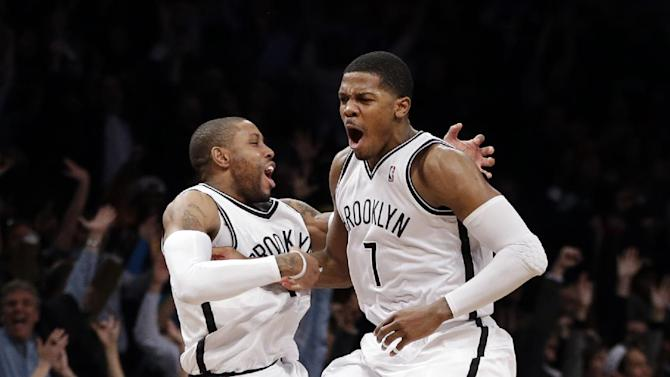 Brooklyn Nets guards C.J. Watson (1) and Joe Johnson (7) celebrate after Johnson scored with time expiring for a 113-111 overtime victory over the Milwaukee Bucks in their NBA basketball game at Barclays Center, Tuesday, Feb. 19, 2013, in New York. (AP Photo/Kathy Willens)
