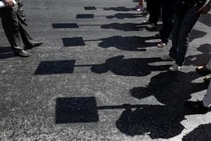 Protesters cast their shadows as they march during an anti-government rally in front of the parliament in Athens