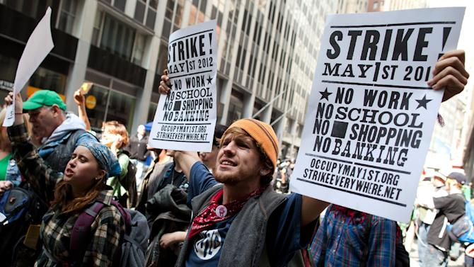 Occupy Wall Street demonstrators march while holding signs near Wall Street to celebrate the protest's sixth month, Saturday, March 17, 2012, in New York.  With the city's attention focused on the huge St. Patrick's Day Parade many blocks uptown, the Occupy rally at Zuccotti Park on Saturday drew a far smaller crowd than the demonstrations seen in the city when the movement was at its peak in the fall. A couple hundred people attended. (AP Photo/John Minchillo)