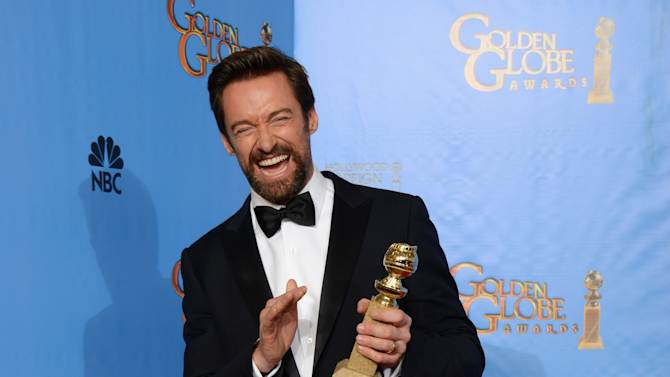 """Actor Hugh Jackman poses with the award for best performance by an actor in a motion picture - comedy or musical for """"Les Miserables"""" backstage at the 70th Annual Golden Globe Awards at the Beverly Hilton Hotel on Sunday Jan. 13, 2013, in Beverly Hills, Calif. (Photo by Jordan Strauss/Invision/AP)"""